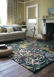 Wool rug decorated with floral and foliage forms in green, navy blue and orange