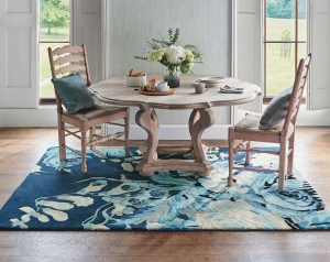 Navy blue rug with large floral design in blue, mint and grey