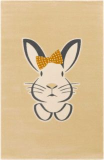 Cream children's rug decorated with a large white rabbit wearing a yellow polka dot bow