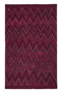 Rectangular red rug decorated with raised woven geometric zig-zag design in red and green yarn