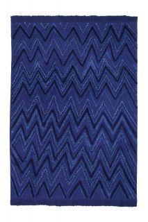 Rectangular blue rug decorated with raised woven geometric zig-zag design in blue yarn