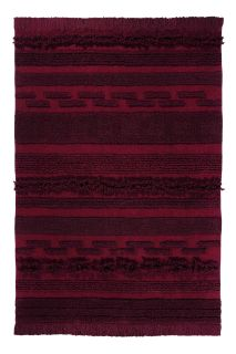 Rectangular red rug decorated with a raised textured stripe pattern
