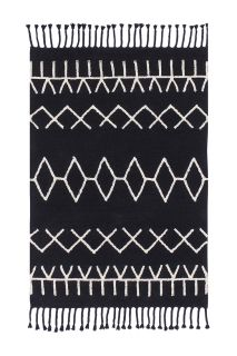 Rectangular black cotton rug decorated with a white geometric tribal design and black braid border
