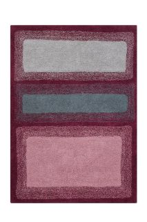 Rectangular shaped red rug decorated with three rounded rectangles in green, blue and pink