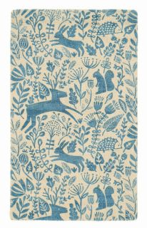 blue wool rug with a delicate woodland design