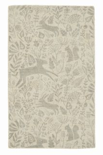 beige wool rug with a delicate woodland design