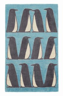 yellow wool rug with a repeat penguin pattern